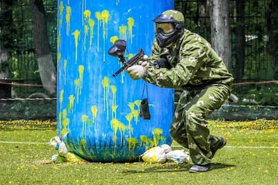 paintball player in front of blue bunker