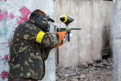 destin paintball player behind wall
